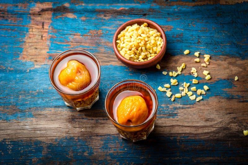 微粒骗局huesillo 由煮熟的剥壳的麦子和干桃子做的传统智利饮料在木板,土气蓝色 免版税库存照片