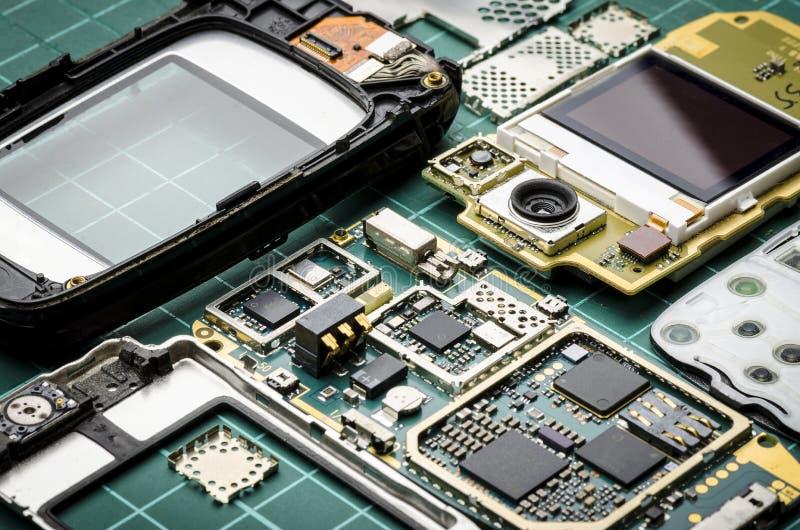 微集成电路、半导体组分和贵重金属在被拆卸的老手机特写镜头的委员会在绿色bac 免版税库存照片