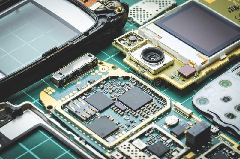 微集成电路、半导体组分和贵重金属在被拆卸的老手机特写镜头的委员会 免版税库存图片