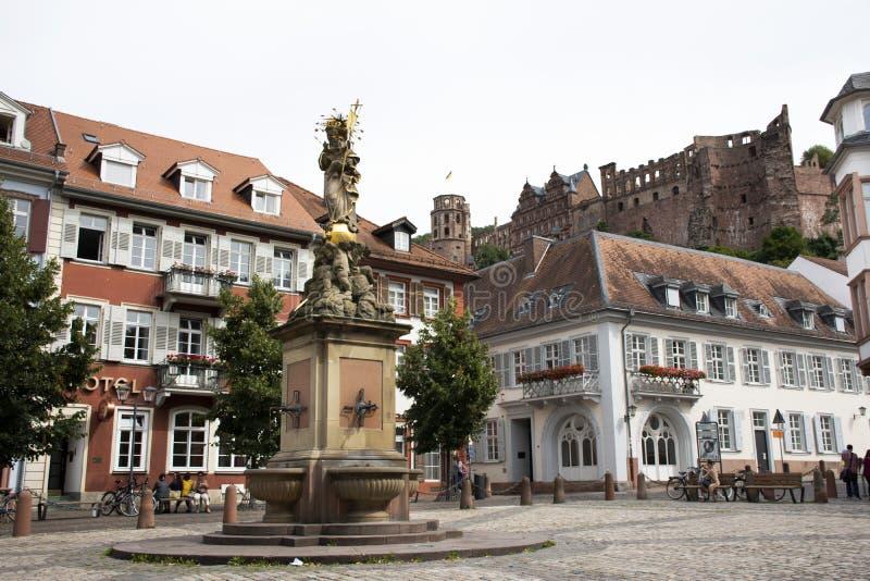 德国人和外国人在玉米市场上的旅客人走和参观madonna雕象在海得尔堡,德国 库存图片
