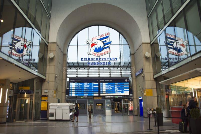 德国人和外国人旅客走和等待火车在曼海姆Hauptbahnhof火车站 库存图片