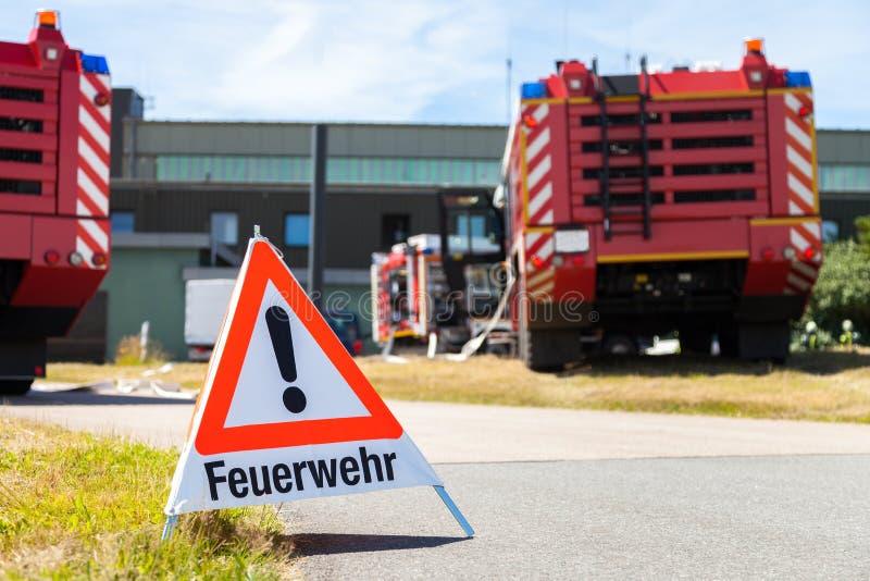 德国人Feuerwehr消防队标志站立近的消防车 免版税库存图片