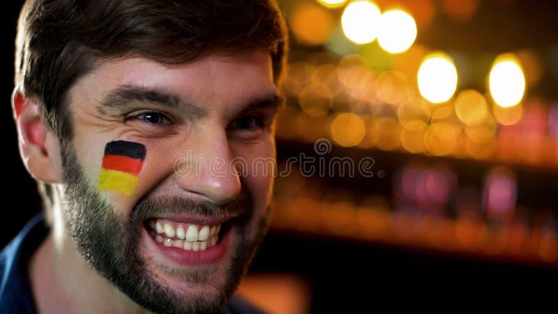 德国体育队的愉快的爱好者与旗子的在面颊微笑的观看的比赛 免版税图库摄影