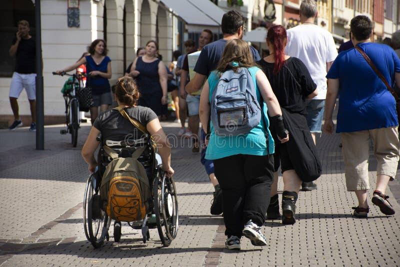 德国在海得尔堡老镇的残疾人和外国旅客走的参观在德国 库存图片