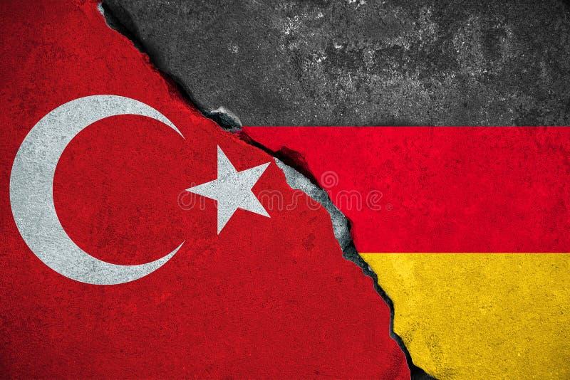 德国对火鸡,在残破的损伤砖墙上的红色火鸡旗子和半德国下垂背景,关系危机政治打仗 库存图片