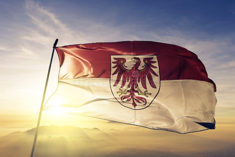 德国旗子纺织品挥动在顶面日出薄雾雾的布料织品勃兰登堡状态  向量例证