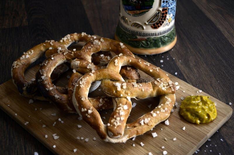 德国椒盐脆饼快餐在木头的啤酒斯坦和芥末 免版税库存照片