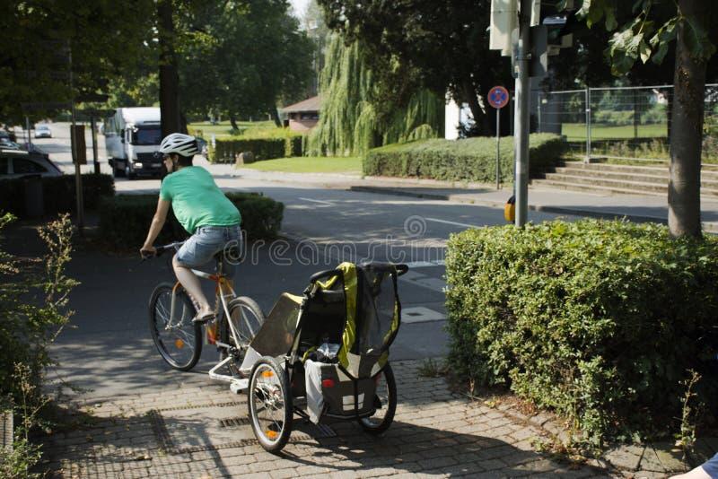 德国母亲婴儿推车的人骑自行车和孩子去回家 免版税图库摄影