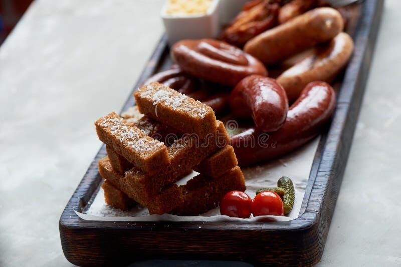 德国热诚的午餐在客栈 烤香肠,被炖的圆白菜,油煎方型小面包片,调味汁 啤酒快餐 库存图片