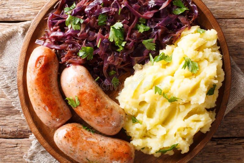 德国烹调:土豆泥、被炖的红叶卷心菜和香肠 免版税库存照片