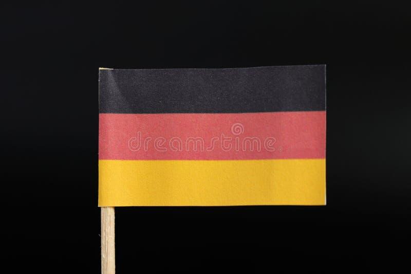 德国的一面原始和正式旗子牙签的在黑背景 一水平三色黑,红色和金子 库存照片
