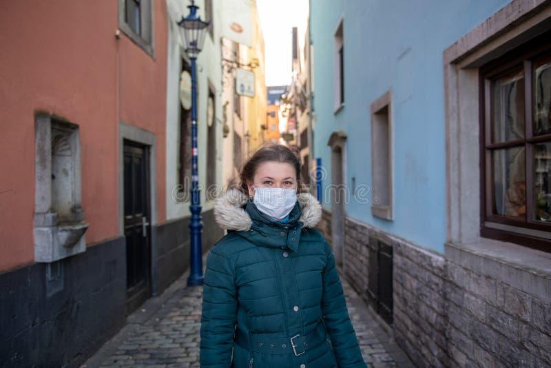 德国老城戴医用面具的女人 库存图片