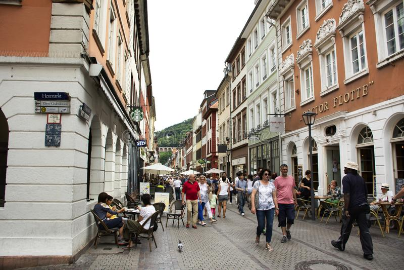 德国走参观的人民和外国旅客和坐在海德尔伯格老镇吃和喝在海得尔堡,德国 免版税库存图片