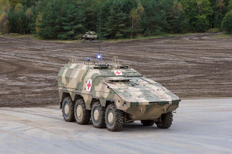 德国GTK拳击手、军医版本从Kmw和Rheinmetall在平台站立在战场附近 库存照片