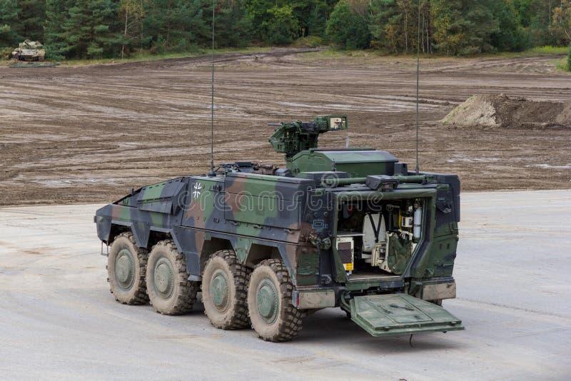 德国GTK拳击手、步兵版本从Kmw和Rheinmetall在平台站立在战场附近 库存图片