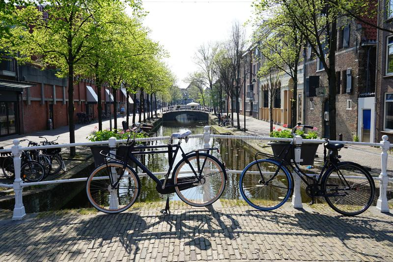 德尔福特,荷兰- 2019年4月21日:在一条历史的运河前面的两辆自行车在德尔福特的中心 库存照片