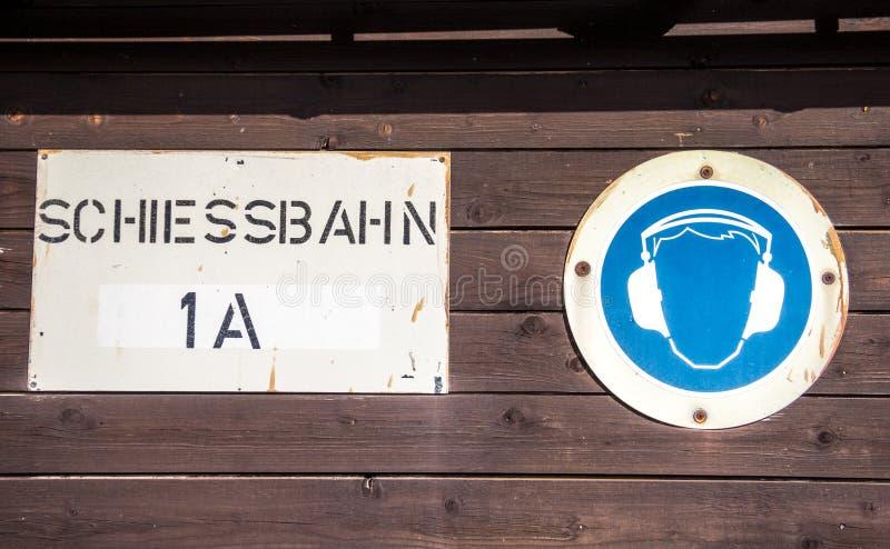 德语Schiessbahn;靶场;与耳朵笨拙的人标志的标志 库存图片