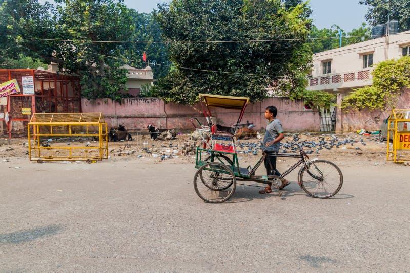 德里,印度- 2016年10月23日:出租机动三轮车人力车和母牛在德里,伊恩迪的中心 图库摄影