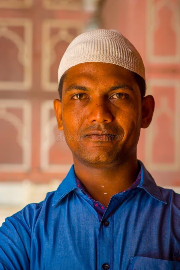 德里,印度- 2017年9月27日:戴一件蓝色T恤杉和一个白色印地安帽子的一个英俊的人的画象,看 免版税库存图片