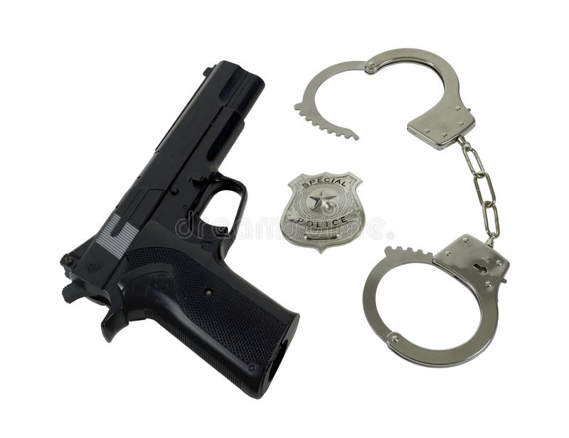 徽章枪把警察扣上手铐 免版税库存照片