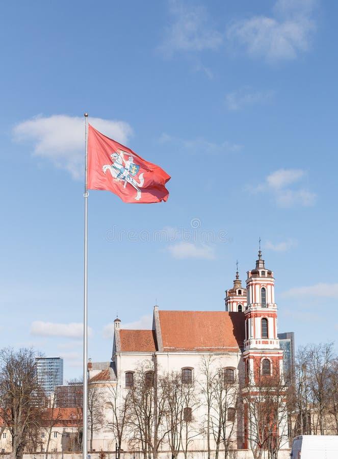 徽章立陶宛旗子的 马的骑士与剑和盾在红色背景 与云彩和教会的天空蔚蓝 库存图片