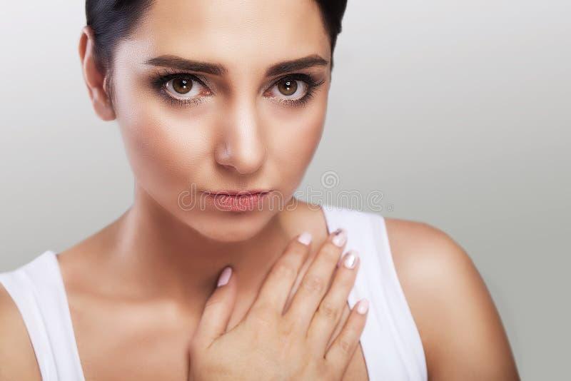 心伤 强的疼痛感觉 女孩握她的在她的胸口寒冷的胳膊 强的咳嗽 健康的概念 在灰色 免版税库存照片