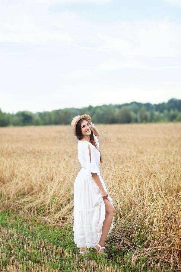 心境的安宁的概念 一可爱的年轻女人在拿着帽子的一块金黄麦田站立 女孩看与轻微 库存图片