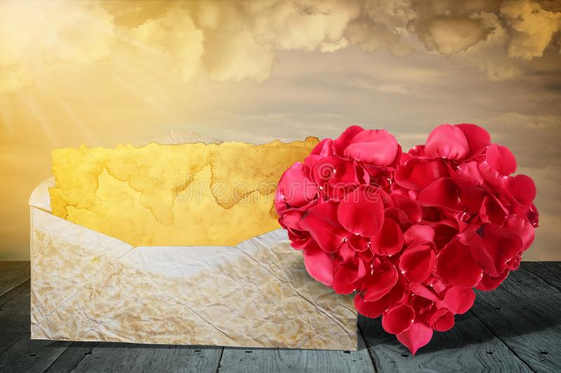 心形由有老信件的玫瑰花瓣做成在木甲板桌 免版税库存照片