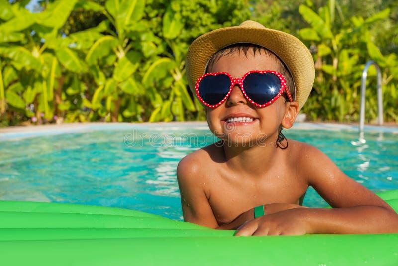 心形的太阳镜的男孩在airbed的绿色 库存照片