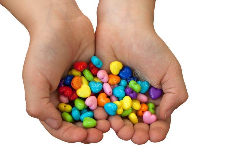 心形的小珠在白色隔绝的手上 免版税库存图片