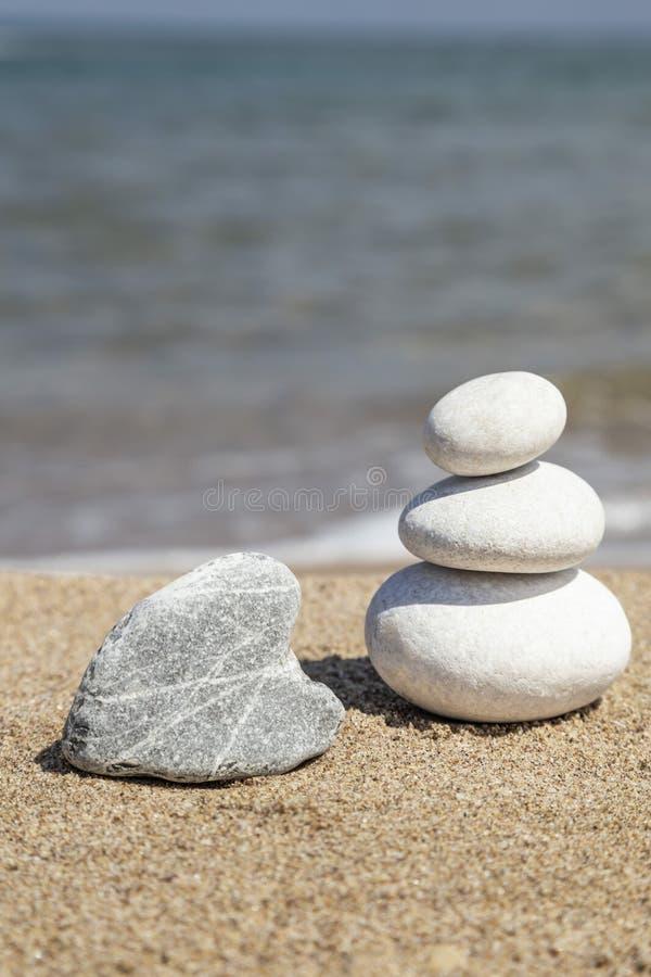心形的岩石和堆总之的小卵石石头在海滩 库存图片