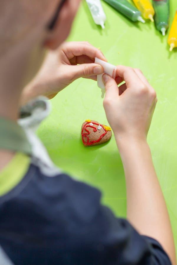 心形的曲奇饼在一张绿色咖啡桌上说谎 儿童的手紧压白色结冰在创造装饰的管外面 免版税库存照片