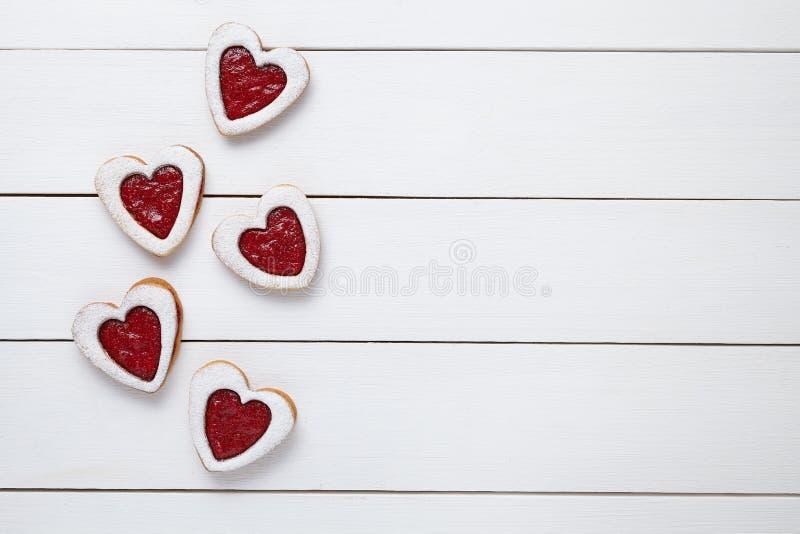 心形的曲奇饼用果酱为在白色木背景的情人节 免版税库存照片