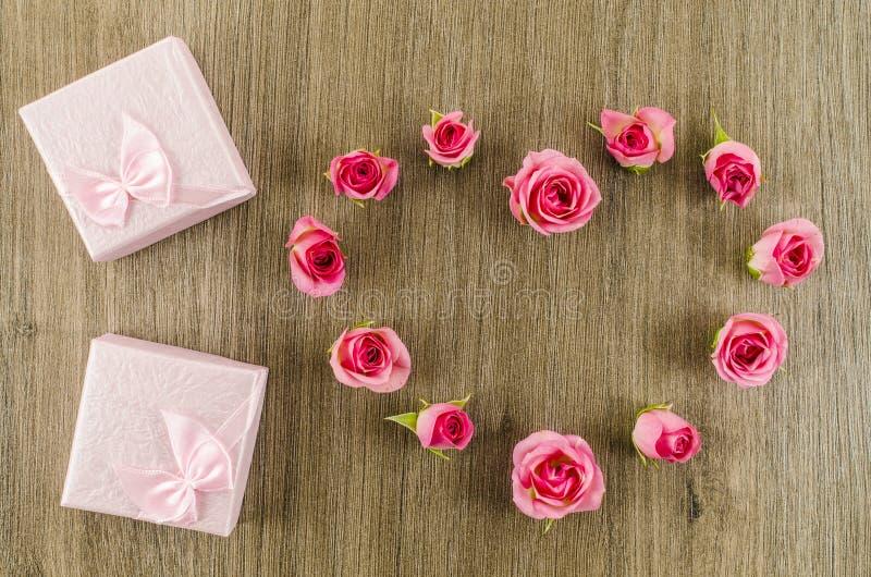 心形的玫瑰色花和礼物盒在木背景 免版税库存照片