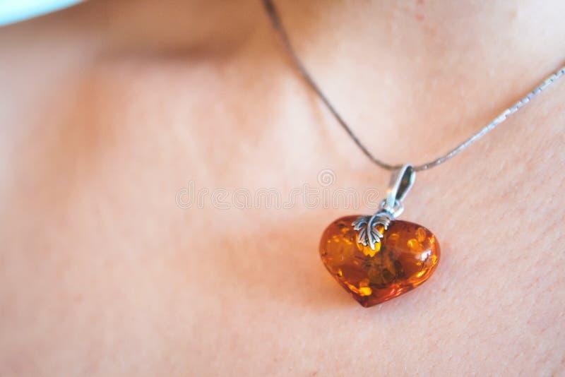心形的琥珀色的垂饰被佩带在年轻女人的脖子上 免版税库存图片