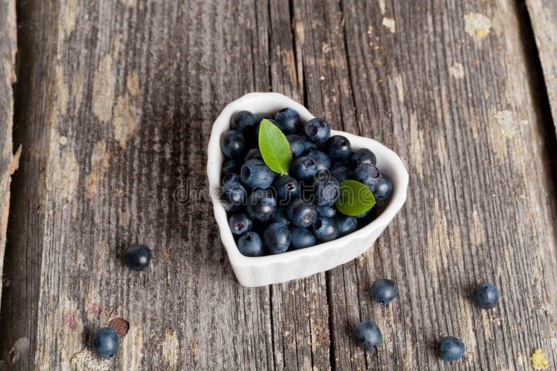 心形的碗在木桌上的蓝莓 库存照片