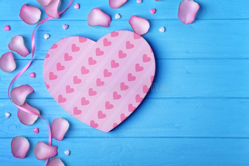 心形的礼物盒和瓣在蓝色木背景 免版税库存图片