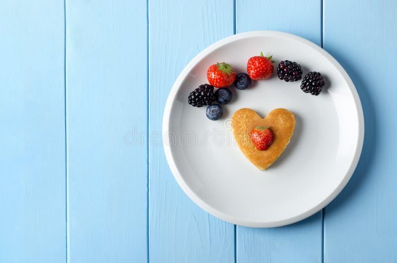心形的薄煎饼用果子从上面在蓝色Planked表上 库存照片