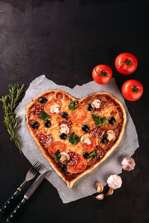 心形的薄饼用蕃茄和蒜味咸腊肠为在葡萄酒的情人节染黑背景 食物概念的浪漫 库存照片