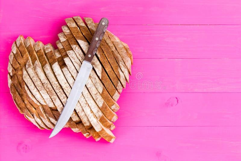 心形的面包和刀子在桃红色背景 库存图片