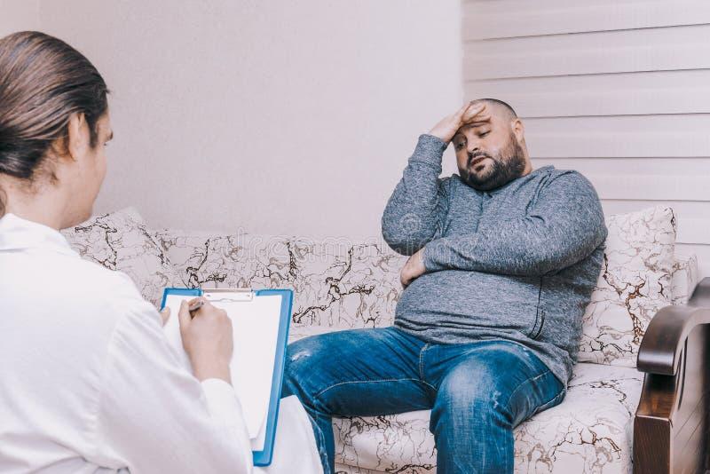 心理治疗家参观的年轻人,谈论他的问题激动,精神健康概念 库存图片