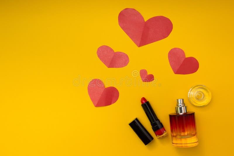 心脏、唇膏和香水在黄色背景 免版税图库摄影