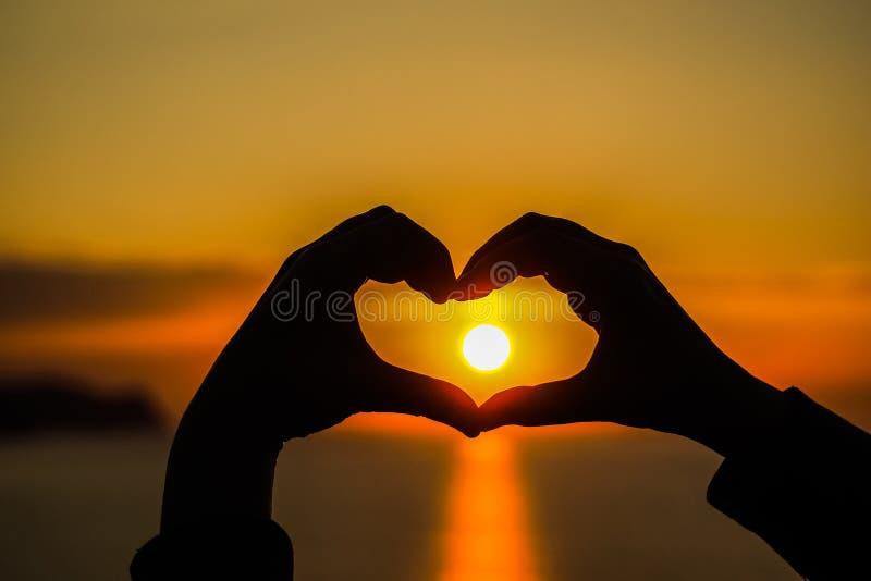 心脏做用有太阳的手在它里面在日落和日出期间 库存图片