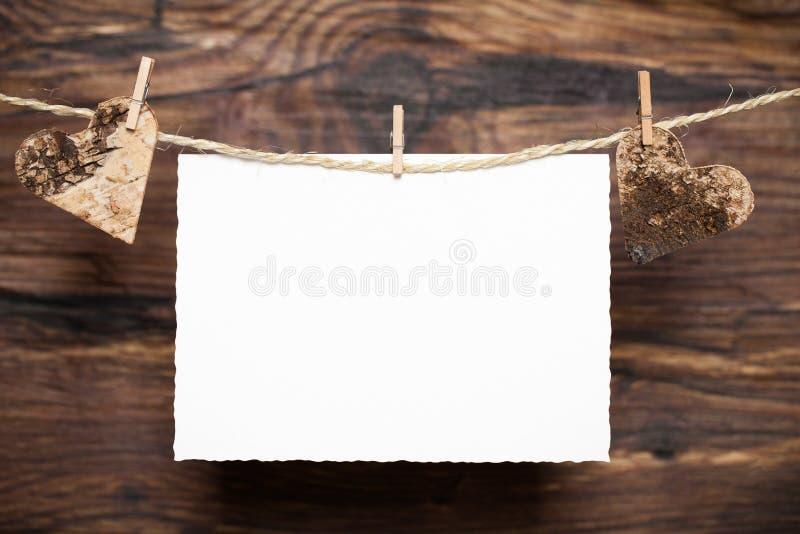 心脏和一张卡片在木背景前面 免版税库存图片