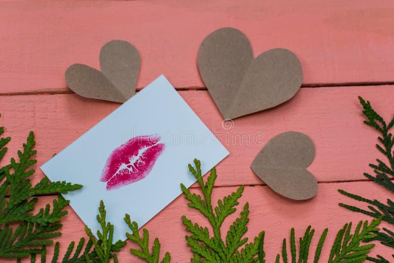 心脏和卡片与嘴唇印刷品在桃红色木背景 库存图片