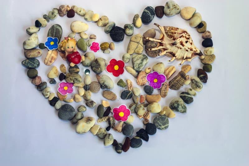 以心脏和壳的形式海石头在白色 免版税库存图片