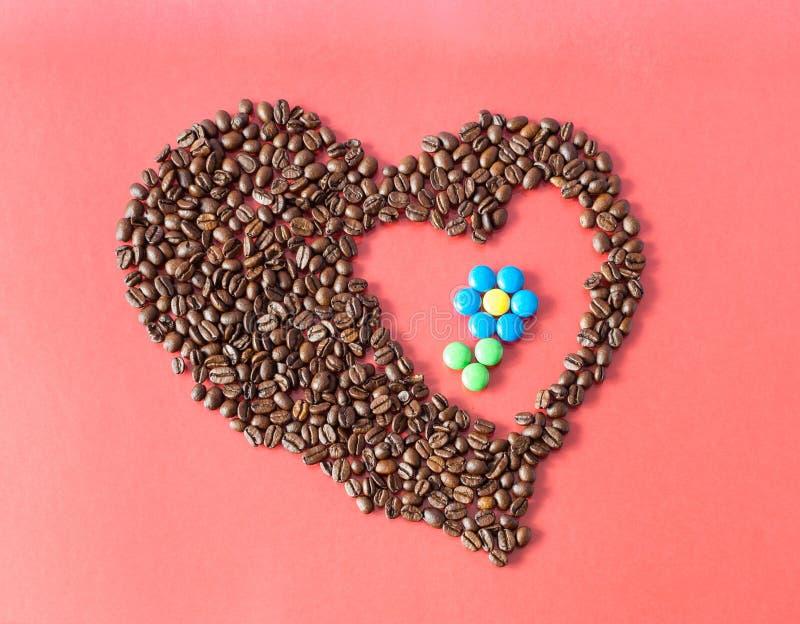 心脏和花组成由咖啡豆和糖果 库存图片