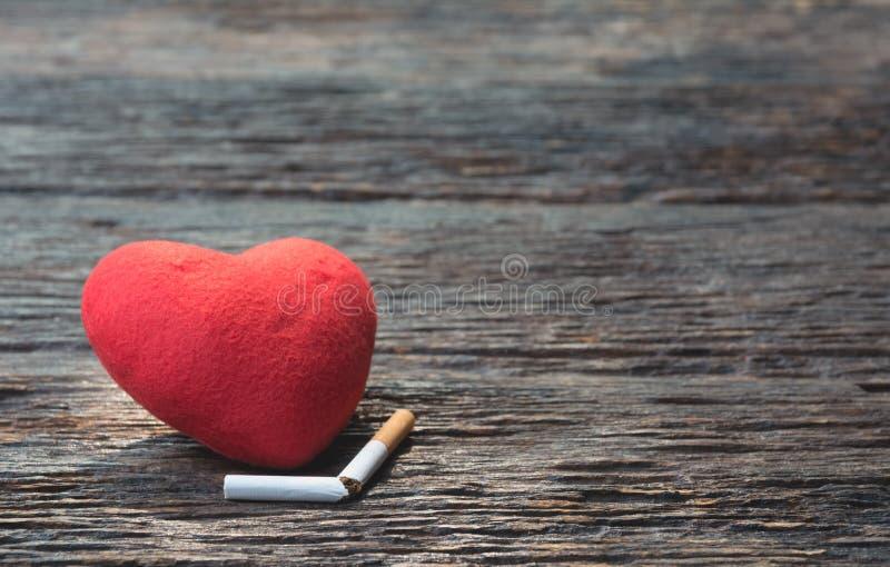 心脏和被切除的香烟在木背景 保护您的h 库存图片