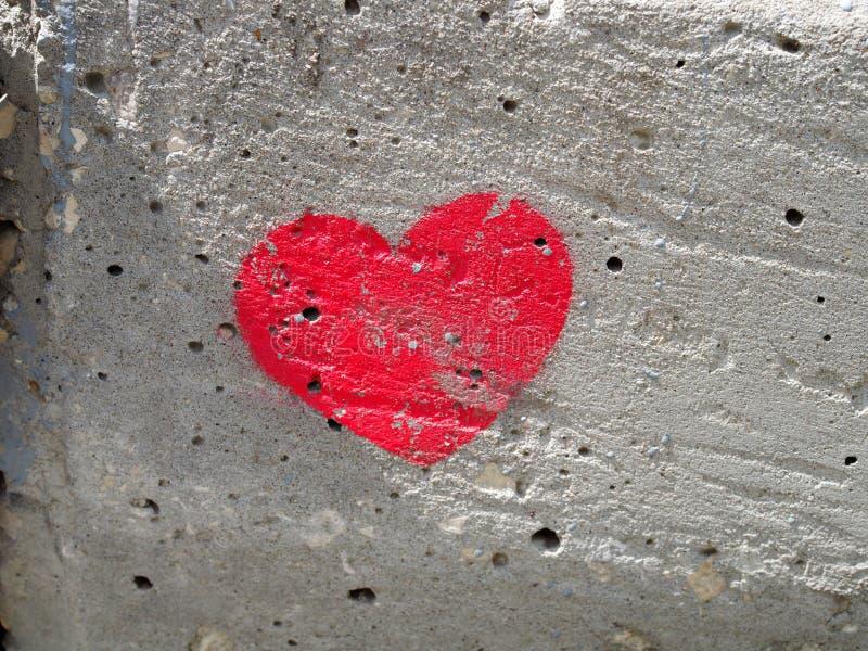 心脏在一个混凝土墙,爱的标志上绘了 库存照片