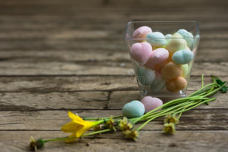 心脏在塑料杯子的形状糖在树木繁茂的背景 免版税库存图片